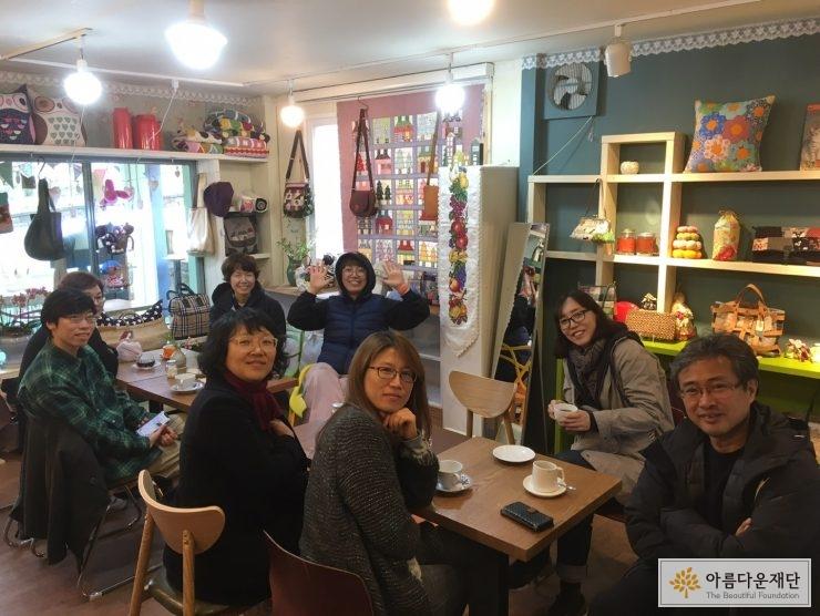 카페에 둘러 앉은 협력 파트너들이 카메라를 향해 밝게 웃고 있다.