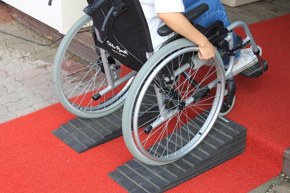 2019변화의시나리오스폰서사업에 선정된 연세대 창업 동아리 MLP의 이동형 경사로를 휠체어가 지나가는 모습