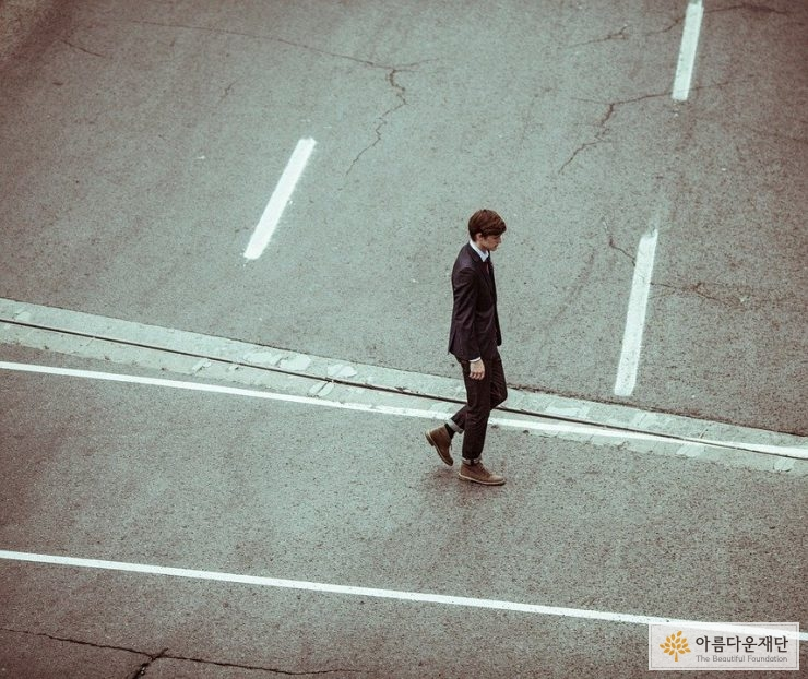 도로 위를 걷는 정장 입은 남자 이미지