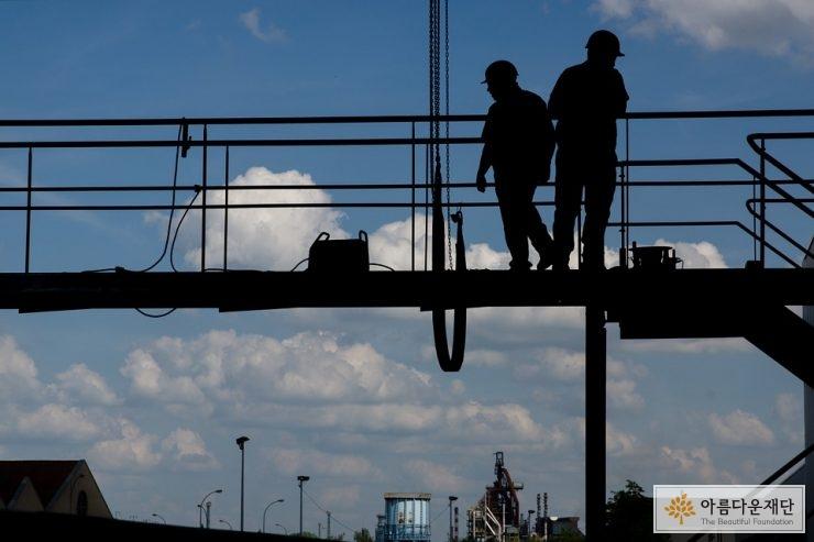 높은 곳에 있는 두 명의 건설 현장 노동자 모습