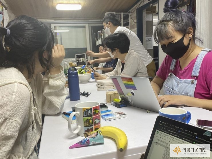 [사진1. 오프라인 참여를 하는 활동가들이 세로로 긴 책상에 모여 앉아있다. 온라인 참여를 하는 활동가들도 있다. 책상 위에는 회의에 필요한 노트북과 화상 회의를 위한 아이패드가 놓여있다. 온라인 참여를 하는 활동가와 오프라인 참여를 하는 활동가가 아이패드로 소통하고 있다.]