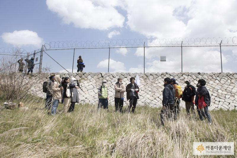 철조망이 있는 제방 아래 들풀에서 모여있는 사람들, 왼편에서는 걷고 있는 모습을 촬영하고 있고 오른쪽에서 왼쪽으로 걸어가고 있다.