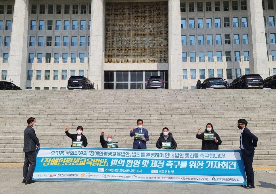 피켓을 든 사람들이 국회 앞에서 장애인평생교육법안 발의 환영 및 제정을 촉구하는 기자회견을 진행하고 있다.