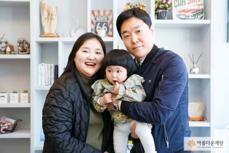 긴 생머리에 검정색 옷을 입은 엄마와 남색 자켓을 입은 아빠 그리고 연두색 원피스를 입은 딸 세 가족이 정면을 보며 찍은 사진