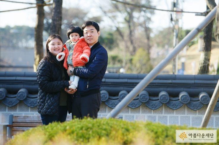 검은색 옷을 입은 엄마와 남색 자켓을 입은 아빠 그리고 주황색 패딩을 입은 딸 아이가 아빠에게 안겨 셋이 찍은 가족사진