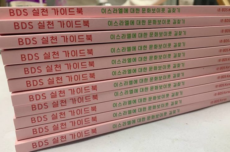 책자가 가득 쌓여 있다. 책등은 옅은 분홍색이며 제목은 'BDS 실천 가이드북: 이스라엘에 대한 문화보이콧 길찾기'이다