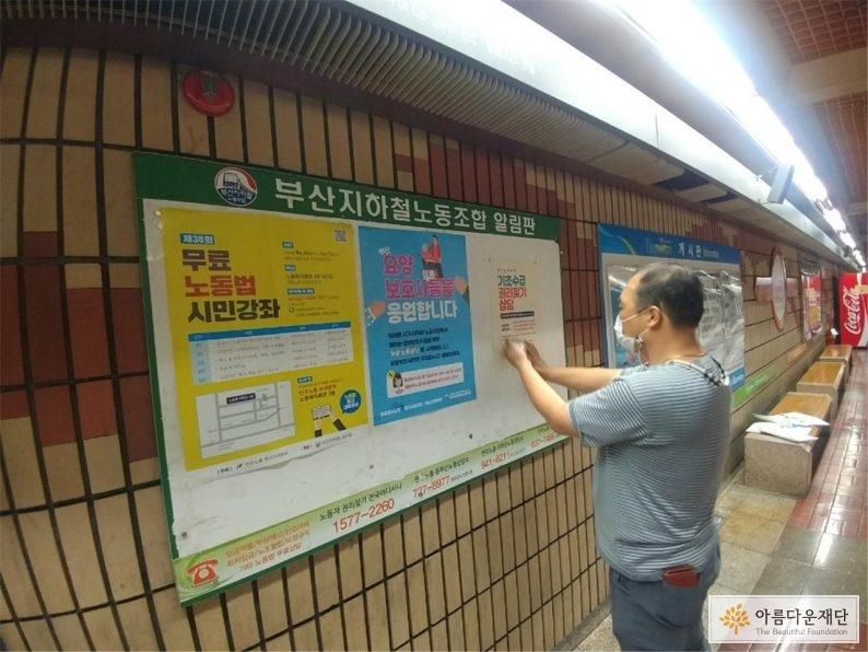 지하철 게시판에 기초수급 권리찾기 전화상담 포스터를 붙이는 사진