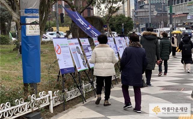 거리를 지나는 시민이 보드 전시를 살펴보고 있다