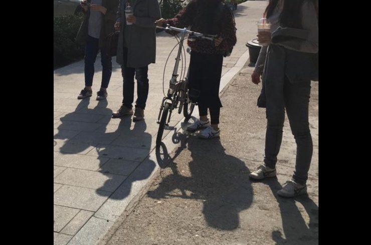 어깨 아래로 구도를 잡아 찍은 네 명의 사람이 있는 이미지. 두 명은 한 손에 음료를 들고 있고, 한 명은 자전거 핸들을 잡고 있다.