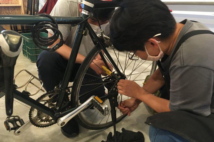 사람 두 명이 자전거 뒷바퀴를 사이에 두고 앉아 체인을 만지며 수리 하고 있다.