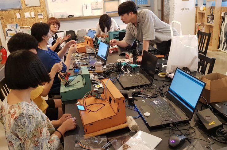 강사님과 참여자들이 아두이노를 이용한 자전거로드 안내판을 만들고 있다. 다섯명의 참여자 앞에 각각 컴퓨터와 조립 키트가 놓여있고, 회색 반팔티를 입은 강사가 설명하고 있따.