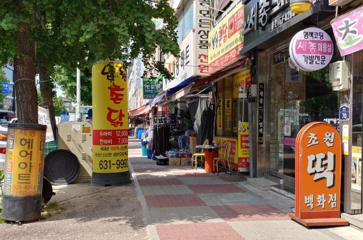 남원 구도심 전경. 마트, 교회, 부동산 등이 있는 작은 거리에 남원 촌닭, 초원떡백화점, 세종헤어아트 입간판에 세워져 있다.